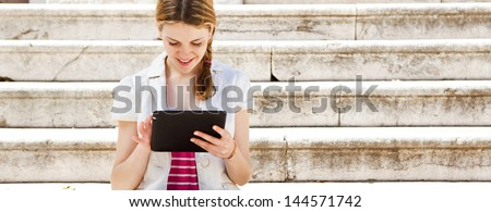Panoramic portrait of a teenager student girl using with her digital tablet to go on-line while sitting down on a university campus entrance stone steps, smiling during  a sunny day. - stock photo