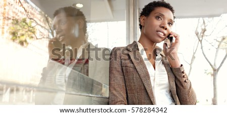 Panoramic portrait of african american business woman, office building with city glass reflections, smiling outdoors. Professional black woman in smart phone conversation call, lifestyle technology.