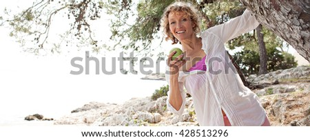 Panoramic portrait of healthy senior woman smiling on a coastal destination, playful around tree trunk, eating a green apple on holiday, nature outdoors. Healthy eating lifestyle, mature woman. - stock photo