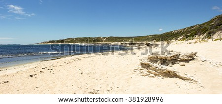 Panoramic  scenic view of the tide ebbing out from the   famous white sandy  surfing beach  at Margaret River south western Australia  on a calm cloudy afternoon in  early summer .