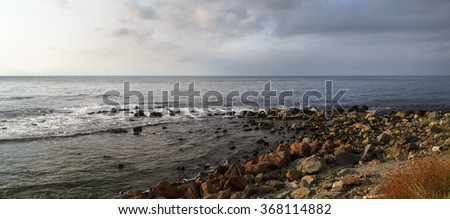 Panoramic seascape. Rocky shore in the foreground. Dramatic sky and the sea. - stock photo