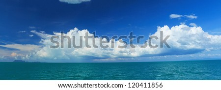 Panoramic seascape with big white clouds,blue sky and green ocean - stock photo