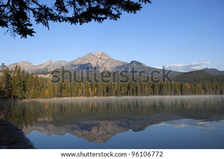 Panoramic shot of mountains reflecting in the lake. - stock photo