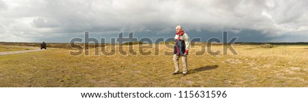 Panoramic shot of senior retired man enjoying the outdoors. Dutch dune landscape with stormy cloudy sky. Lonely man. The Netherlands. Wadden island. Texel. - stock photo