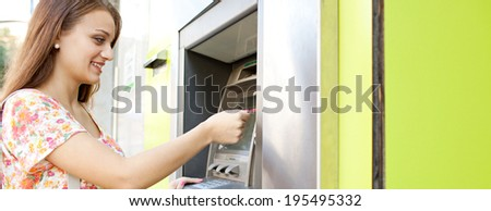 Panoramic side portrait of an attractive young woman using a cash point machine with her credit card to withdraw money while shopping in a city and carrying bags. Consumerism and lifestyle, outdoors. - stock photo