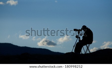 Panoramic Silhouette of Big Game Hunter / Wolf Watcher / BIrd Watcher using spotting scope telescope optics to view distant wildlife from a folding chair, with blue sky and clouds in the background  - stock photo
