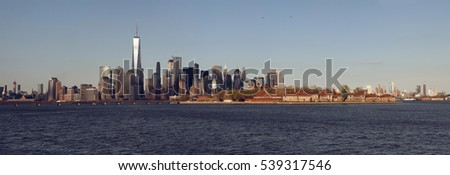 Panoramic sunset view of New York skyline with Ellis Island. USA.