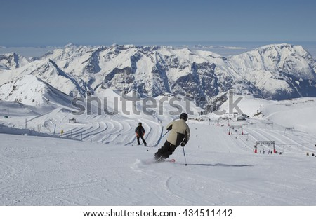 Panoramic view from the glacier in Les Deux Alpes, France in the Alps in Europe, showing a man skiing on a nursery ski slope, chairlift, snow covered mountains with clouds below them and blue sky.  - stock photo