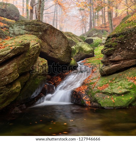 Panoramic view of a beautiful autumn waterfall. - stock photo