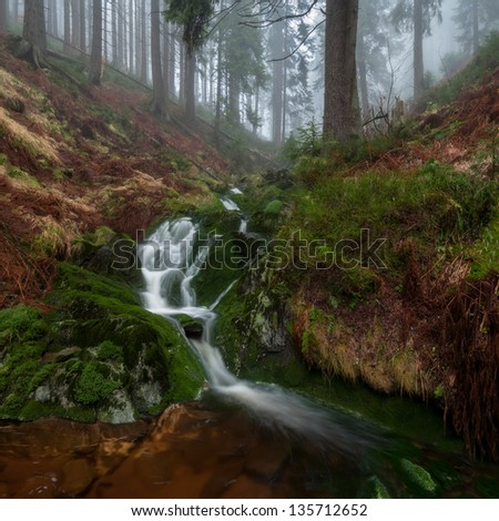 Panoramic view of a beautiful autumn waterfall. - stock photo