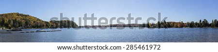panoramic view of a lake with a boat and houses under the sun of the indian summer - stock photo