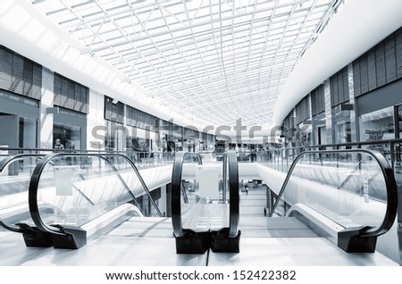 panoramic view of a modern mall and escalator, blue toned - stock photo