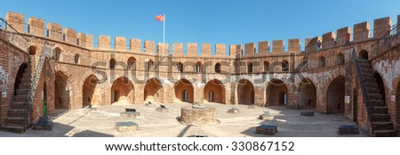 Panoramic view of Alanya Red Tower in Antalya  with orenge bricks, on bright blue sky background. - stock photo