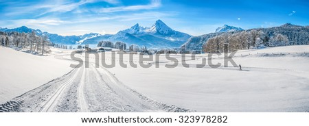 Panoramic view of beautiful winter wonderland landscape in the Bavarian Alps with cross-country slopes and famous Watzmann massif in the background, Nationalpark Berchtesgadener Land, Bavaria, Germany - stock photo