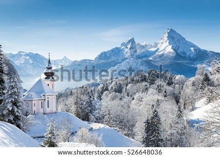 Panoramic view of beautiful winter wonderland mountain scenery in the Alps with pilgrimage church of Maria Gern and famous Watzmann summit in the background, Berchtesgadener Land, Bavaria, Germany