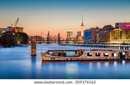 Panoramic view of Berlin skyline with famous TV tower and Oberbaum Bridge with old ship wreck lying in river Spree in twilight during blue hour at dusk, Berlin Friedrichshain-Kreuzberg, Germany - stock photo