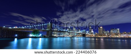 Panoramic view of Brooklyn Bridge and New York City skyline at night - stock photo