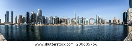 Panoramic view of business bay and downtown area of Dubai reflection in a river. - stock photo