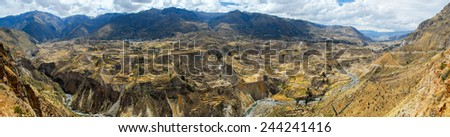 Panoramic view of Colca Canyon, Peru, South America. The Incas built farming terraces with ponds over the cliff. One of the deepest canyons in the world. - stock photo