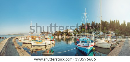Panoramic view of colorful fishing boats docked in the harbor of Kalami, Corfu island, Greece