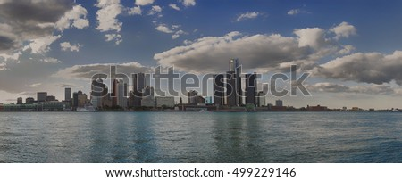 Panoramic view of Detroit skyline and river with dramatic clouds