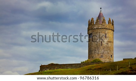Panoramic view of Doonagore Castle on a overcast day in summer, county Clare, Ireland. - stock photo
