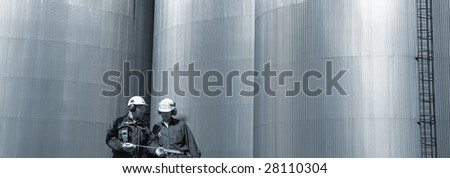 panoramic view of engineers in front of fuel storage tanks, blue toning. - stock photo