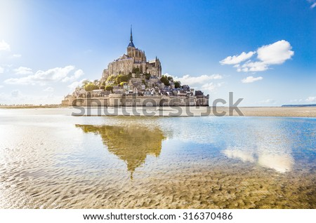 Panoramic view of famous Le Mont Saint-Michel tidal island on a sunny day with blue sky and clouds, Normandy, northern France - stock photo