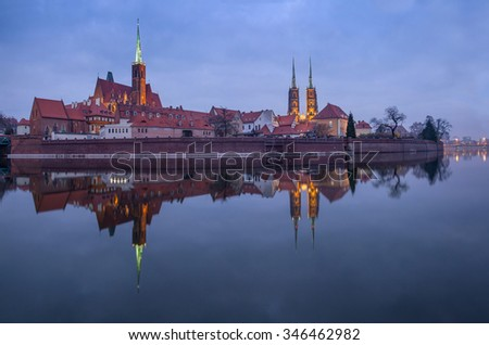 Panoramic view of famous old island Tumski with cathedral of St. John reflection in the Odra river at dusk. Wroclaw, Poland, EU. A long time shutter exposure. - stock photo