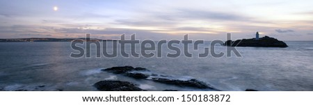 Panoramic view of Godrevey Island and its lighthouse looking out towards the lights at St Ives - stock photo