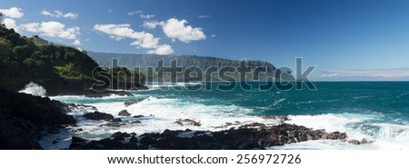 Panoramic view of Hanalei Bay and Na Pali mountains as waves crash against shore near Queens Bath at Princeville, Kauai, Hawaii - stock photo