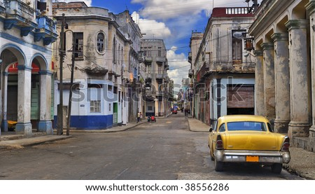 Panoramic view of Havana street with crumbling buildings and old classic car - stock photo