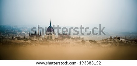 Panoramic view of he house of hungarian parliament building in foggy weather and blurred foreground, Budapest, Hungary - stock photo
