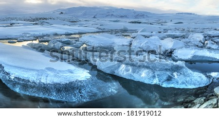 Panoramic view of icebergs in Jokulsarlon glacial lagoon and Breidamerkurjokull glacier on a sunny winter's afternoon in Iceland (HDR) - stock photo