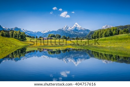 Panoramic view of idyllic summer landscape in the Alps with clear mountain lake and fresh green mountain pastures in the background - stock photo