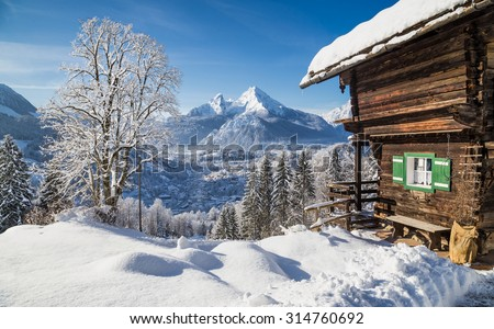 Panoramic view of idyllic winter mountain scenery with traditional mountain chalet in the Alps on a sunny day with blue sky - stock photo