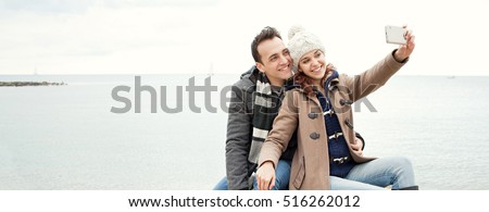 Panoramic view of joyful tourist couple on beach, posing with heads together taking selfies on a winter holiday, smiling fun. Young couple using smart phone technology, travel lifestyle, outdoors.