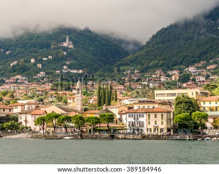 Panoramic view of Lenno town with Chiesa di Santo Stefano, Santuario Madonna del Soccorso Church from the ferry in the middle of Lake Como under Dramatic Sky Fog on Mountain in Lombardy, Italy