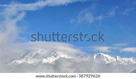 panoramic view of Mont-Blanc on the clouds under blue sky - stock photo