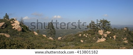Panoramic view of mountains, evergreens and boulders, California - stock photo