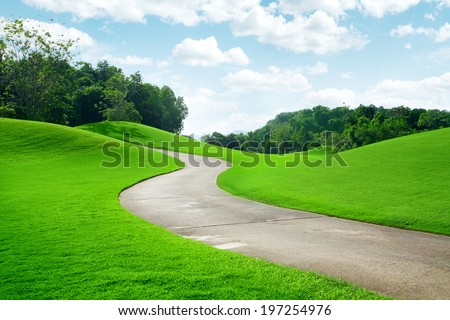 panoramic view of nice green hill and path  on blue sky background - stock photo