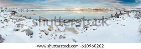 Panoramic view of norwegian lake at sunset. There are stone columns on covered with snow rocks.