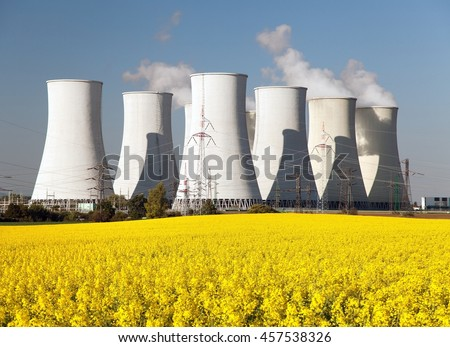Panoramic view of Nuclear power plant Jaslovske Bohunice with golden flowering field of rapeseed - Slovakia - two possibility for production of electric energy - stock photo