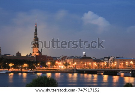 Panoramic view of Old Riga, Latvia - stone bridge and a church at night