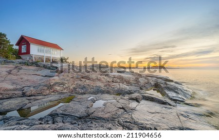Panoramic view of red house at seafront in morning light, filters applied. Grisslehamn, Sweden - stock photo