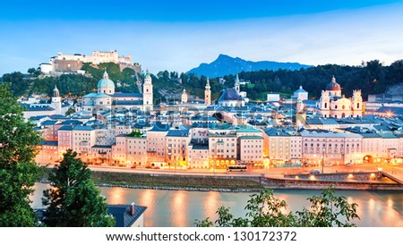 Panoramic view of Salzburg skyline with river Salzach at dusk as seen from Kapuzinerberg in Salzburg, Salzburger Land, Austria - stock photo