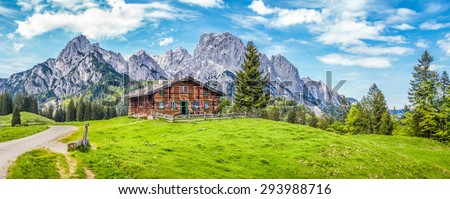 Panoramic view of scenic mountain landscape in the Alps with traditional old mountain chalet and fresh green meadows in springtime - stock photo