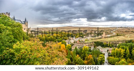 Panoramic view of Segovia Castle (Alcazar of Segovia) in the historic city of Segovia with summer landscape and dramatic thunderclouds, Castilla y Leon, Spain