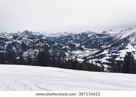 Panoramic view of snow covered alpine mountains with rugged peaks surrounding a forested valley on a cold grey winter day with snowy slope in the foreground - stock photo