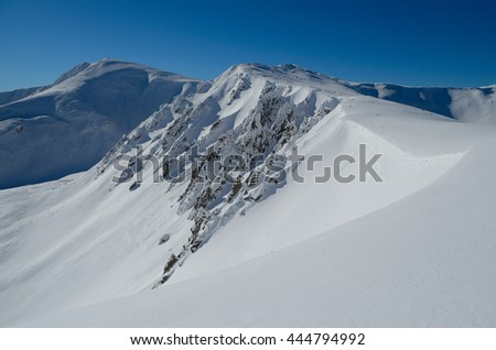 Panoramic view of snowy mountains in clear winter day